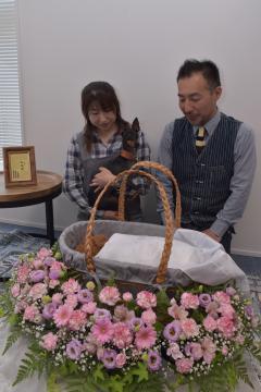 花を飾り付けた籠の中にペットの遺体を納めた家族葬のイメージ。右は吉鹿隆司さん=つくば市内