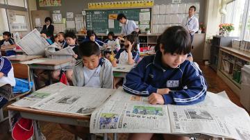 新聞を開いて見出しの工夫を探る児童たち=筑西市立古里小