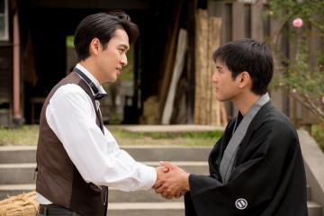 映画の一場面。企業側の加屋淳平(左)と固い握手を交わす住民代表の主人公・関根三郎=(c)2019Kムーブ