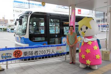 キララちゃんバス(後方)の乗客200万人目になった藤田三恵子さん=JR土浦駅前