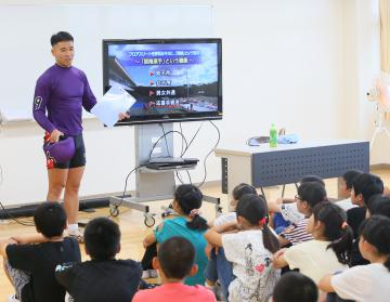 競輪選手の須賀和彦さん(左奥)の話を聞く取手東小の児童=取手市吉田