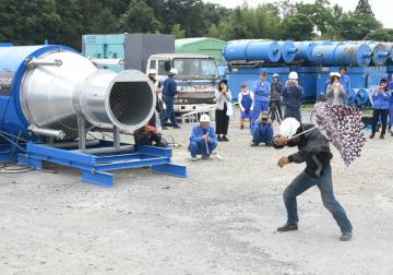 大型送風機(左)から送り出された秒速80メートルの風に、傘をあおられるスタントマンの男性(右)=筑西市花田