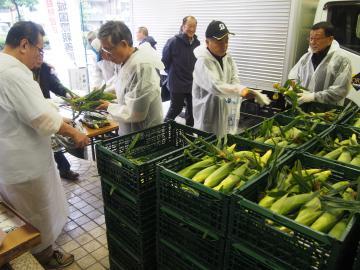 結城市産のトウモロコシを配布する関係者たち=東京都新宿区四谷
