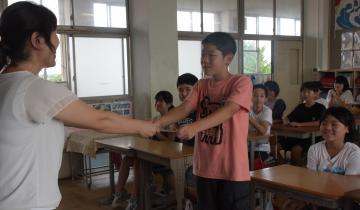 少し緊張した表情で担任の先生から通知表を受け取る児童=ひたちなか市津田東