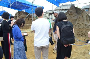サンドアートイベントの砂像制作者から話を聞く参加者=日立市河原子町