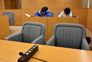 開放された境町議会の議場で、議員席に着いて自習する町立境一中の生徒ら=22日午後2時半ごろ、境町