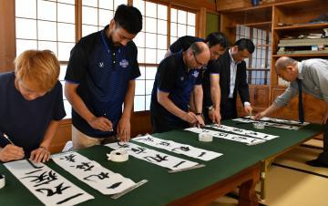 漢字表記のスローガン「一丸疾走」を書く選手ら=水戸市酒門町の書魁社
