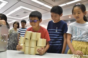 模擬紙幣を使って1億円の重さを体験する参加者=結城市中央町の市民文化センターアクロス