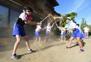 綱を地面に打ち付け、先祖の霊を家に送り届ける子どもたち=13日午後、行方市三和、吉田雅宏撮影