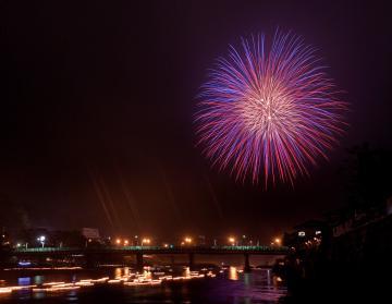 久慈川を流れる灯籠の光の帯と打ち上げられた花火=14日午後7時59分、大子町大子