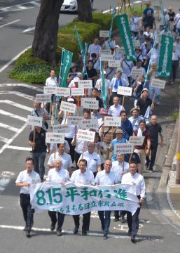横断幕やプラカードを手に平和な社会の実現を訴える参加者=日立市の平和通り