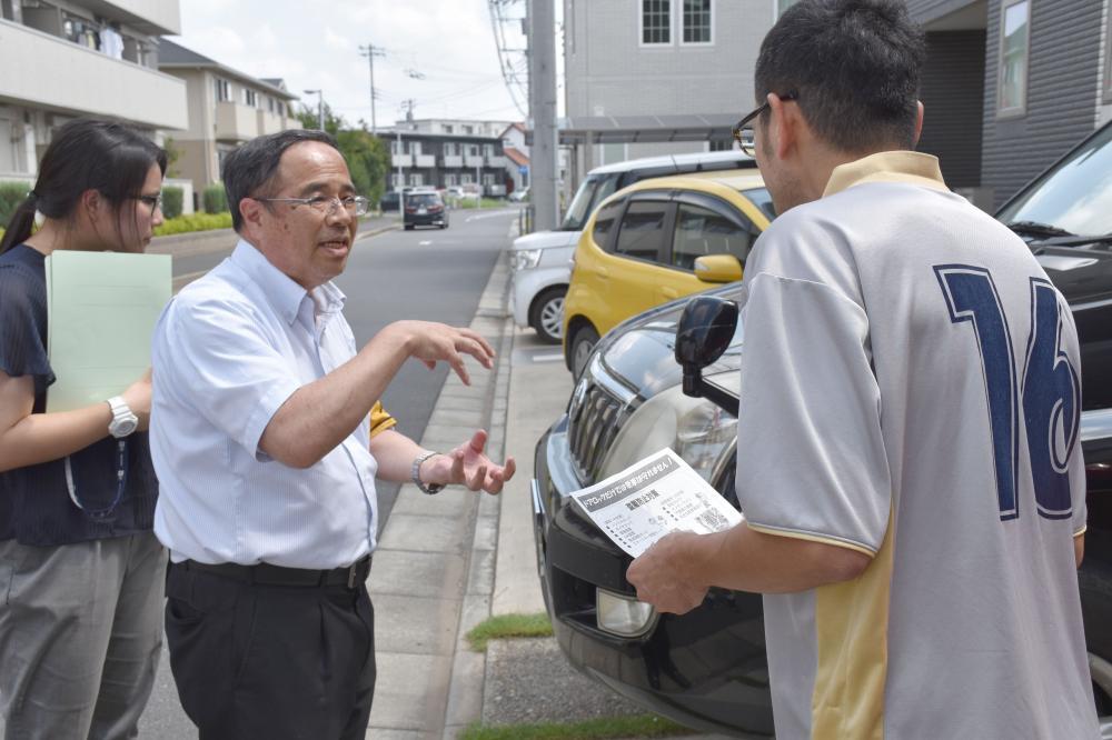 住宅を訪問し、車の防犯対策を呼び掛けるつくば中央署員(左)=つくば市学園の森