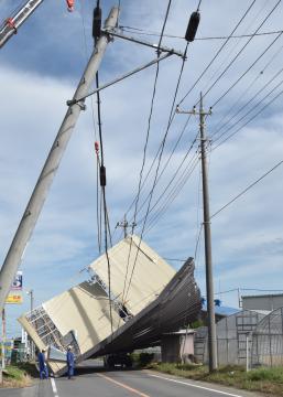 台風の影響で県道側に倒れた物置。電柱も傾いている=八千代町磯、小林久隆撮影