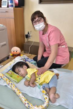 利用者の子どもに寄り添う菊池遥加さん=筑西市幸町の重症心 身障害児デイサービス施設「きなり」