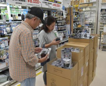 台風19号接近に備え、ホームセンターでランタンの購入を検討する夫婦=9日午後、鹿嶋市和