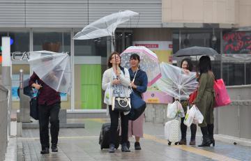 風に傘をあおられたり、傘を斜めにしたりしながら歩く人たち=12日午前11時38分、水戸市宮町、吉田雅宏撮影
