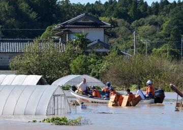 消防団の水難救助船により救出される住民=13日午前10時41分、水戸市岩根町、吉田雅宏撮影