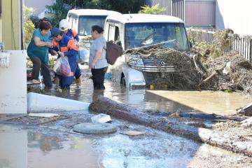 久慈川の水があふれ、浸水した家屋から助け出される住民の母娘=13日午前9時50分ごろ、常陸大宮市富岡