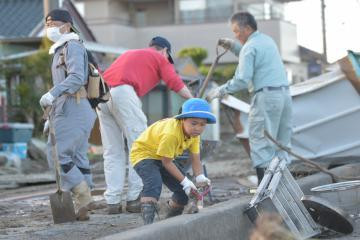 久慈川の堤防決壊現場付近で、道路を覆った泥をスコップでかき出す人たち=13日午後4時ごろ、常陸大宮市富岡、小野寺晋平撮影