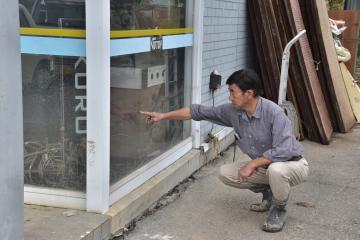 床上浸水の位置を指し示す電器店の後藤茂さん=15日午前、常陸太田市新地町