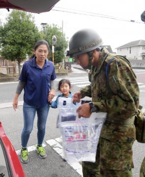 給水所で被災者の車に水を運び込む自衛隊員=15日午後1時26分、常陸大宮市北町、吉田雅宏撮影