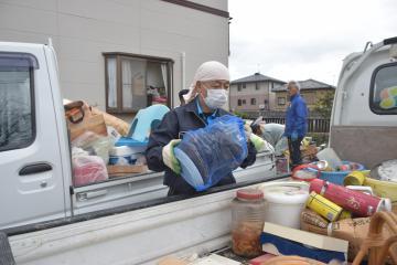 浸水した住宅の後片付けを手伝う住民=15日午後0時35分、ひたちなか市枝川