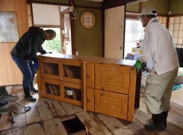 床上浸水した民家では、家具を運び出す作業が急ピッチで行われた=16日午後0時40分ごろ、常陸太田市松栄町、鹿嶋栄寿撮影