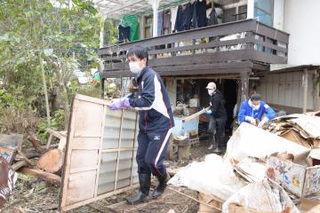浸水被害を受けた民家から泥だらけの家財道具を運び出す災害ボランティアら=18日午後2時半ごろ、大子町大子