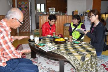 被災者の健康状態などを尋ねる保健師(右側2人)=常陸太田市上高倉町