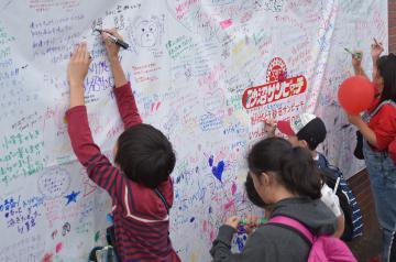 「ありがとう砂沼サンビーチ」の横断幕にメッセージや絵を描く子どもたち