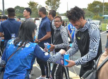 町田戦の試合前、募金活動を行う本間幸司(右)ら=20日、ケーズデンキスタジアム水戸