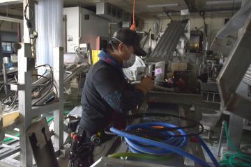 浸水した生産ラインのモーターを調べる水戸冷凍食品の男性従業員。工場内では洗浄作業が進む=21日午後、水戸市飯富町