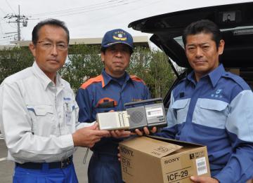 神達岳志常総市長からラジオを受け取った高梨哲彦大子町長、石井邦一県議(右から)=大子町役場