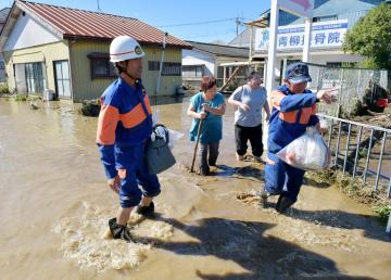 浸水家屋から助け出され、久慈川から流れ込む水の中を歩く母娘=13日午前9時50分、常陸大宮市富岡