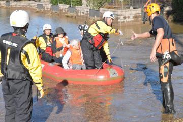 消防隊のボートで救助される被災者=13日、水戸市藤井町