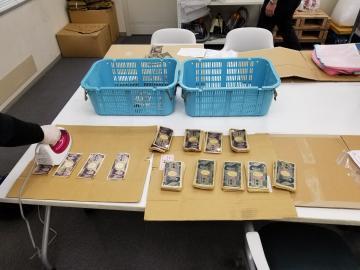 常陽銀行では、浸水被害のあった顧客から預かった貨幣を洗浄し、アイロンで乾かす作業が進められている(同行提供)