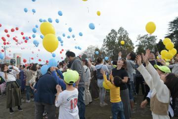 花の種とメッセージを添えた風船を一斉に放つ八俣小の児童や保護者たち=古河市東山田
