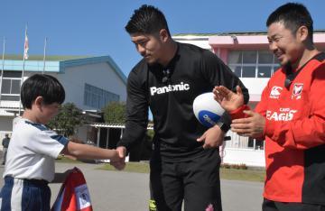 常陸大宮市立上野小学校を訪問し、児童と握手する松田力也選手(中央)と田中史朗選手(右)=5日午前、同市根本
