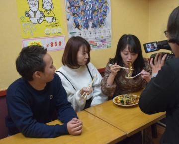 撮影でスタミナラーメンを食べる出演者ら=ひたちなか市元町