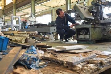 浸水被害に遭った常磐工作所。社長の藤咲充則さんが工作機械の被害状況を確認する=7日午前11時ごろ、常陸太田市松栄町、鹿嶋栄寿撮影