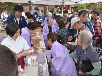 天皇陛下の即位を祝い、参拝客に餅を振る舞う鹿島神宮の氏子ら=鹿嶋市宮中