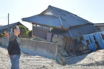 久慈川の水が押し寄せ、地盤が削られ家が傾いた広木賢さん。住宅再建に向け悩みは深い=8日午前10時55分ごろ、常陸大宮市小倉、鹿嶋栄寿撮影