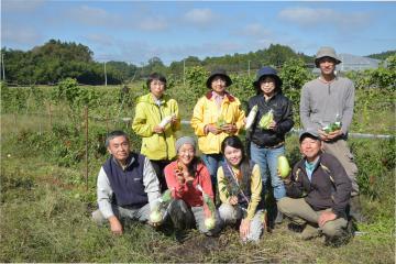 専門店を運営する涌井義郎代表理事(前列左)とあした有機農園で作業する生産者ら=笠間市小原