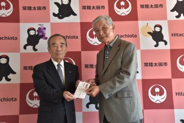 石田正喜会長(右)が大久保太一市長に義援金を手渡した=常陸太田市役所