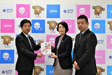 高橋靖市長(左)に目録を手渡す鈴木由紀子専務=水戸市中央