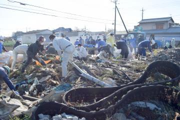 不法投棄された大量の廃棄物を拾い集める参加者ら=石岡市杉の井