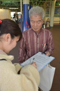署名を集める「市民合意の駅名改称を願う会」のメンバー(奥)=3日午後4時15分ごろ、JR佐貫駅