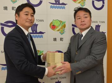 境町にふるさと納税として2千万円寄付した金太郎ホームの佐々木和博社長(右)=境町役場