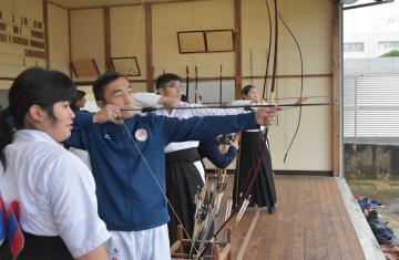 弓道部員(左)から指導を受けるモンゴルの空手代表選手=城里町春園の県立水戸桜ノ牧高常北校