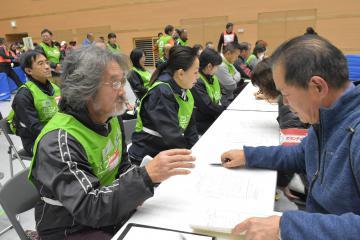被災者役(左)から支援の要望を聞き取る参加者=水戸市緑町
